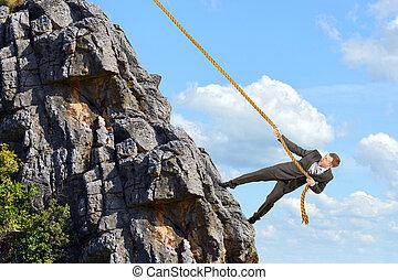 Business man climbs mountain