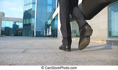 Business man commuting to work. Confident guy in suit being on his way to office building. Young businessman with a briefcase walking in city. Slow motion Rear back view Close up