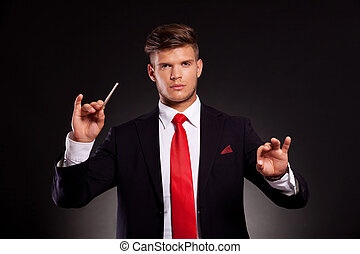 business man conducting orchestra - young business man...