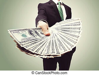 Business Man Displaying a Spread of Cash over a green ...