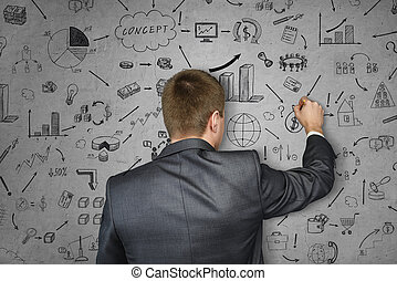 Business man drawing on concrete wall