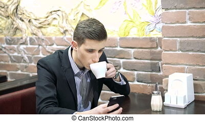Business man drinking a cup of coffee while sitting with his phone in cafe.
