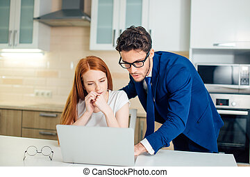 Business man explaining something to woman with laptop