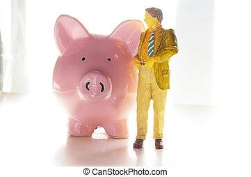 Business man figure next to pink piggy bank