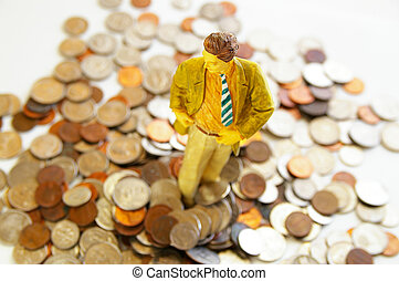 business man figure standing in a pile of money