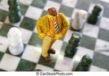 business man figure standing on a chess board