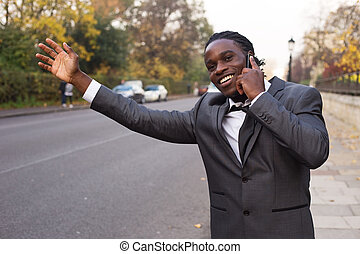 business man hailing a taxi on the phone.