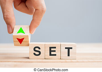 business man Hand change wood cube block with SET text (The Stock Exchange of Thailand) to UP and Down arrow symbol icon. Interest rate, stocks, financial, ranking, interest rates and Cut loss concept