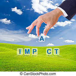 business man hand made impact word buttons on green grass meadow