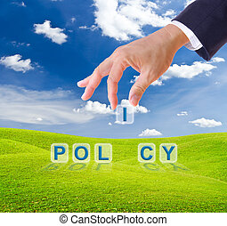 business man hand made policy word buttons on green grass...