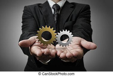 3d cogs as concept - business man hand shows 3d cogs as...
