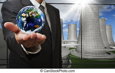 the earth and nuclear power plant - business man hand shows...