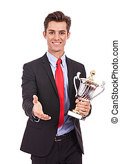 business man handing a trophy  and handshaking