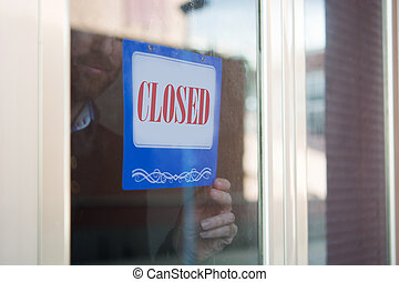 Business man hanging closed sign