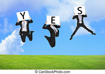 Business man happy jumping with yes text on the green grass