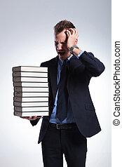 business man has headache from books
