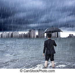 business man holding an umbrella and standing  with cloudburst