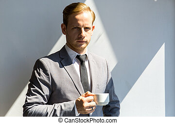 Business man holding cup of coffee