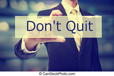 Business man holding Don't Quit on blurred abstract background