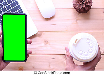 business man holding green screen smartphone with coffee cup on office table desk background