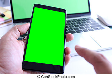 business man holding green screen smartphone with point on office desk table background