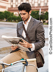 Business man holding newspaper on a bicycle