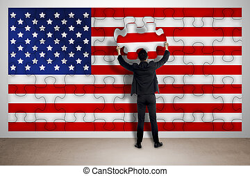 Business man holding piece of puzzle, making USA flag