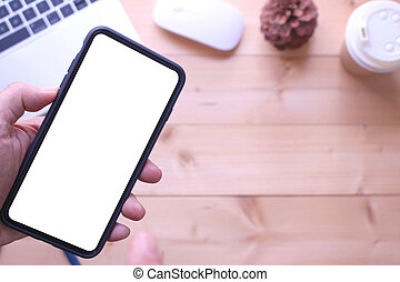 business man holding smartphone on office table desk background