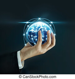 Business man holding the small world in his hands on dark background, Elements of this image furnished by NASA