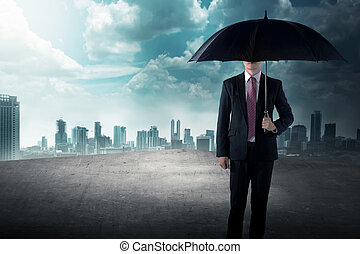 Business man holding umbrella standing on the rooftop