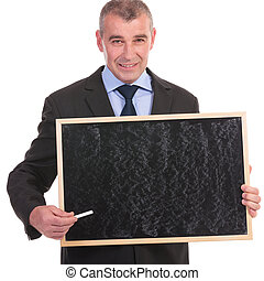 business man holds a small blackboard and points with chalk