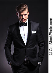 business man holds both hands in pockets - elegant young...
