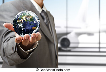 "business man holds globe in the airport""Elements of this image furnished by NASA"""