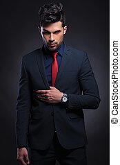 business man holds hand on suit lapel