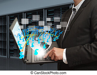 business man holds laptop computer and social network in server room