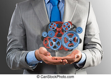 business man holds up a mechanism of gears