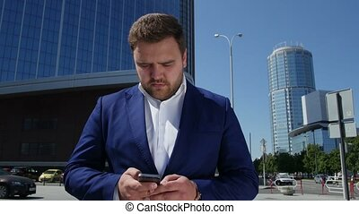 Business man in blue suit dials the phone number on the street. 4k