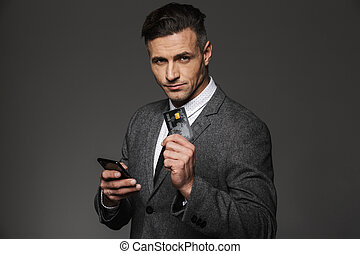 Business man in formal clothing demonstrating plastic credit card and holding cell phone in hand, isolated over gray background