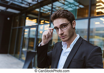 Business man in glasses near the office looking at camera