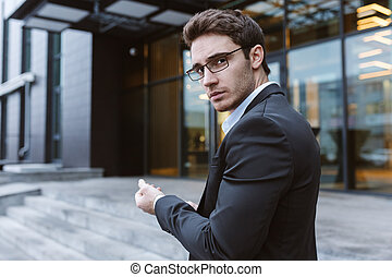 Business man in glasses standing sideways and looking at camera