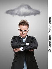 Half-length portrait of business man in glasses with arms crossed standing under stormy cloud, isolated on grey