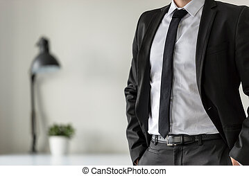 Business man in his office with his hands in the pockets of his suit