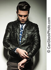 Business man in leather jacket, looking down while fixing his sl