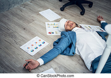 Business man in suits lying unconscious on the floor in the office