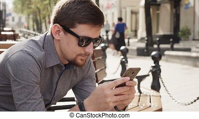 Business man in sunglasses uses smartphone to work on sunny morning in city