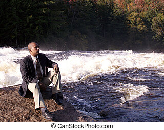 business man in a suit sitting on a rock in front of a rushing river