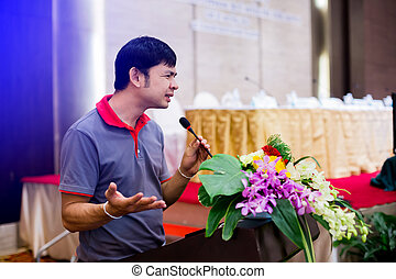 Business man is making a speech in front of a big audience
