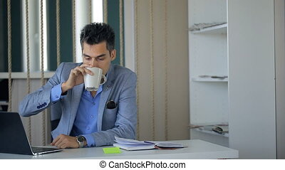 Business man is taking coffee break sitting at workplace continuing working.