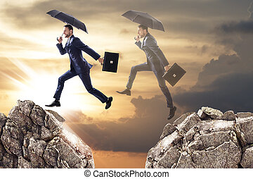 Business man jumping over a cliff with umbrella.