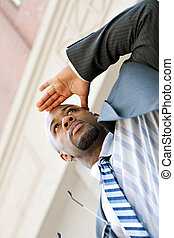 Business Man Looking Ahead - A young business man holds his...